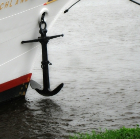 anchor hanging on side of boat near shore