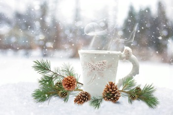 Ceramic mug with steam rising form it nestled in in a sprig of pine and pinecones in the snow