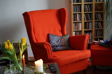 Red armchair near a bookshelf and an end table with a lit candle.