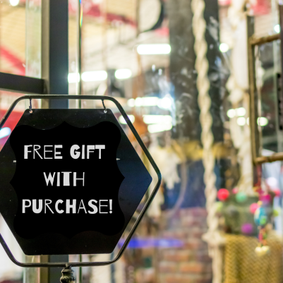 Store front with a sign outside that says free gift with purchase