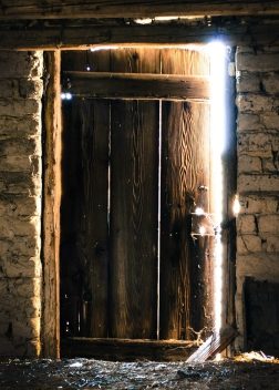 wooden door slightly ajar revealing bright light on the other side
