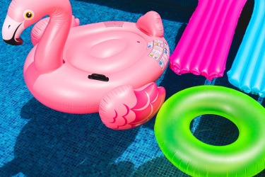 pool with an inflatable flamingo raft, two standard lounge rafts and a tube, all bright colors.